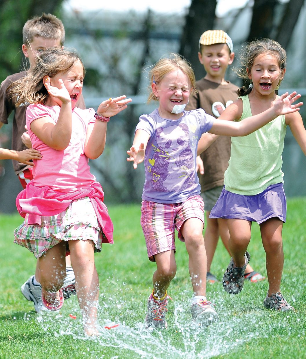 Campers Grace Alfone, right, and Charley Lodwick get splashed by a water balloon during the second annual Camp Olympics at Soda Creek Elementary School on Tuesday afternoon.
