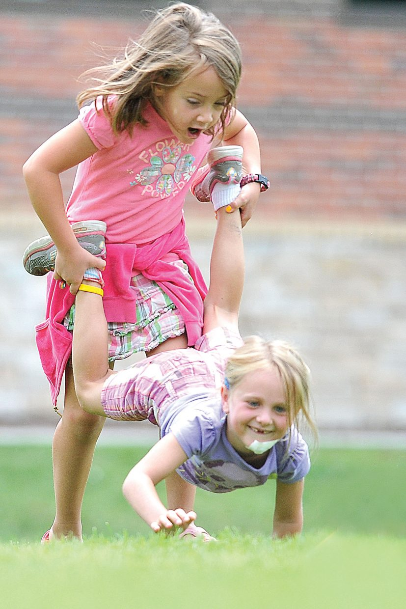 Campers Grace Alfone, standing, and Charley Lodwick take part in the wheelbarrow race during the second annual Camp Olympics at Soda Creek Elementary School on Tuesday afternoon. Several summer camp programs took part in the Camp Olympics, which included a variety of events including the cookie races, wheelbarrow races, obstacle courses and a water balloon launch.