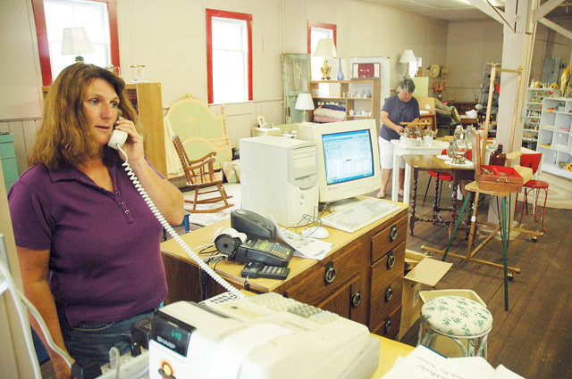 Vicki Morgan talks on the phone inside Affordable Furnishings and Collectibles. Morgan closed the store in January and has reopened with plans to make the shop into more of a general store.