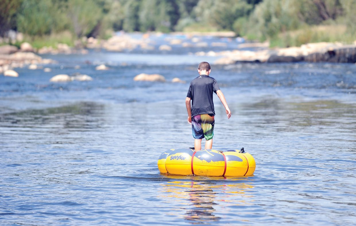 Michael Keough, from Des Moines, Iowa, stands on his tube Thursday afternoon as he floats down the Yampa River. Recent rains have helped river levels remain steady and prolonged the tubing season for visitors and locals.
