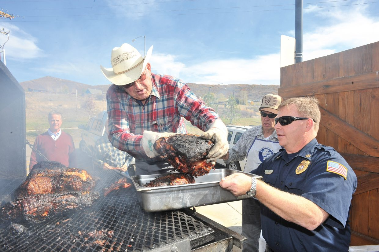 North Routt Fire Protection District Chief Bob Reilley, right, works at the annual Republican Pig Roast in October 2012.