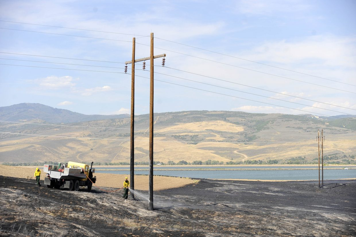 West Routt Fire Protection District firefighters spray water on power line poles that caught fire in the wildfire Friday near the Hayden Station power plant.