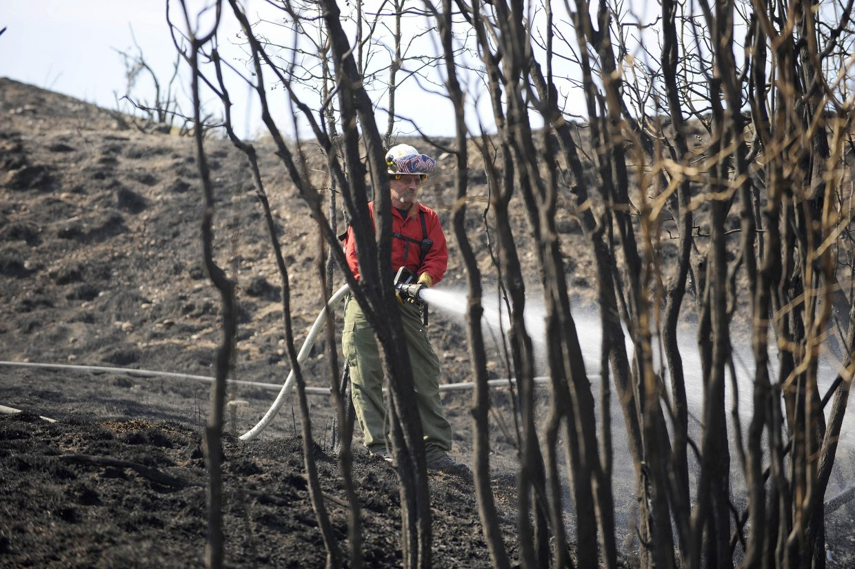 Oak Creek Fire Protection District Chief Chuck Wisecup works the wildfire near the Hayden Station power plant Friday.