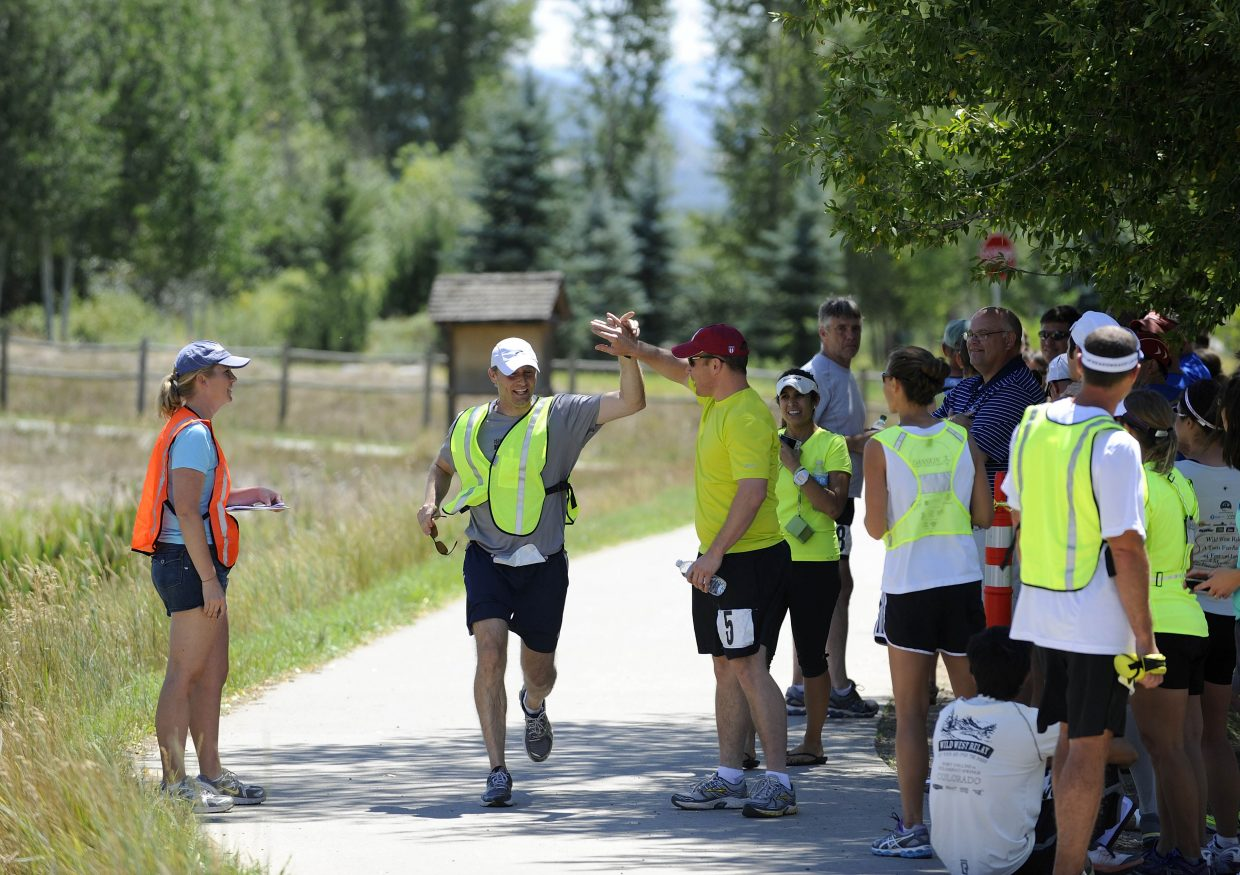 Chris Manske, of Houston, center, tags teammate Jim Wyncoop, of San Diego, on Saturday at the River Creek Park in Steamboat Springs during the Wild West Relay. The relay began Friday in Fort Collins and took 200 runners into Wyoming, back down to Colorado and into Steamboat, where they finished at Strawberry Park Elementary School.