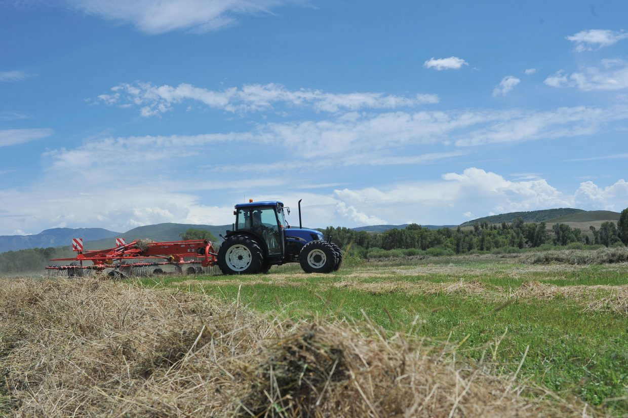 Rancher Michael Hogue rakes hay on a ranch west of Steamboat Springs.