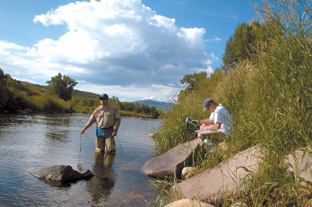 Colorado Division of Wildlife fisheries biologist Billy Atkinson and assistant Dave Dietrich test the Yampa River for dissolved oxygen in summer 2004. The extreme drought of 2002 caused trout in the Steamboat Springs stretch of the Yampa to bunch up near the mouth of Fish Creek, where the cold water held more oxygen.