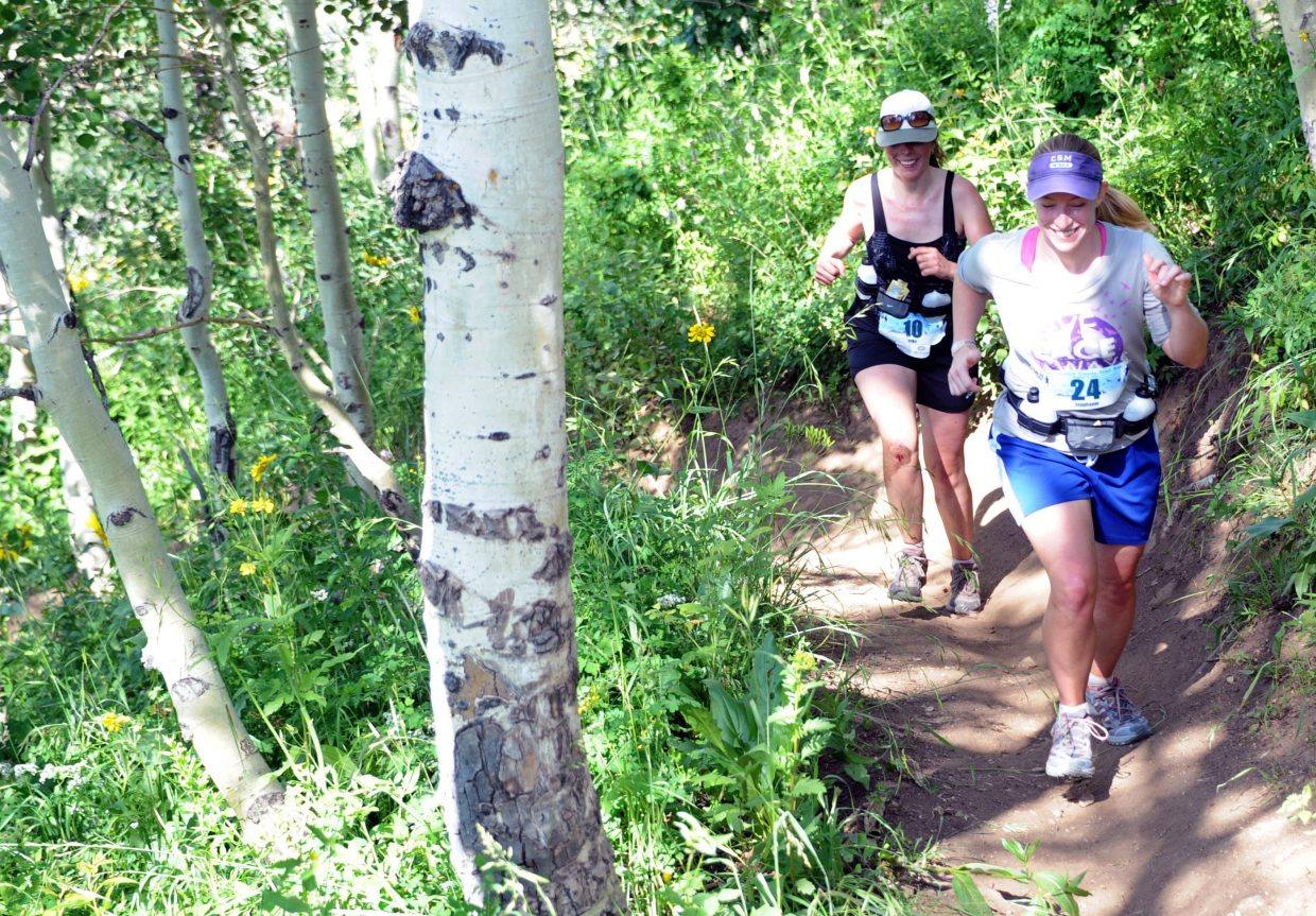 Stephanie Johnson, front, and Erika Anderson fight their way up a steep section of trail Saturday in the Mount Werner Classic.