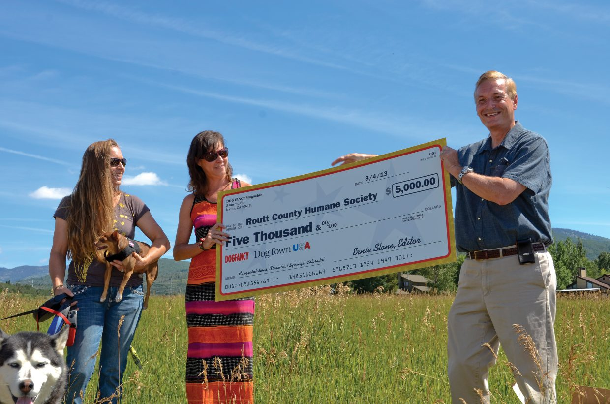 Holly Larson, from left, and Molly Waters, co-presidents of the Routt County Humane Society, accept a check for $5,000 from Ernie Slone, editor of Dog Fancy magazine, on Saturday during a ceremony recognizing Steamboat Springs as Dog Town USA. The annual award was given based on criteria including the presence of dog-friendly activities, restaurants, businesses, dog parks, medical specialists and pro-dog legislation, according to a release from the magazine.
