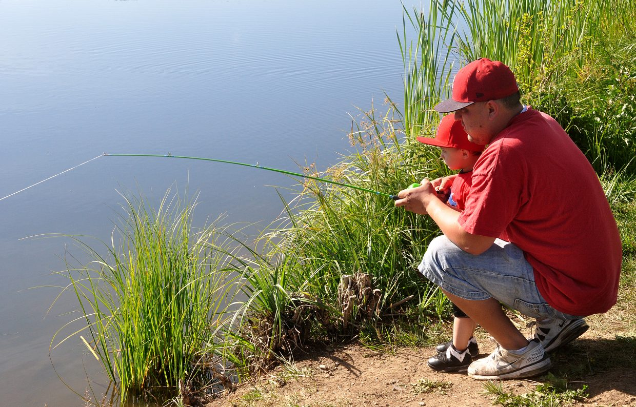 Brandon Cook teaches his son Javon, 2, to fish for trout Tuesday morning at Casey's Pond.