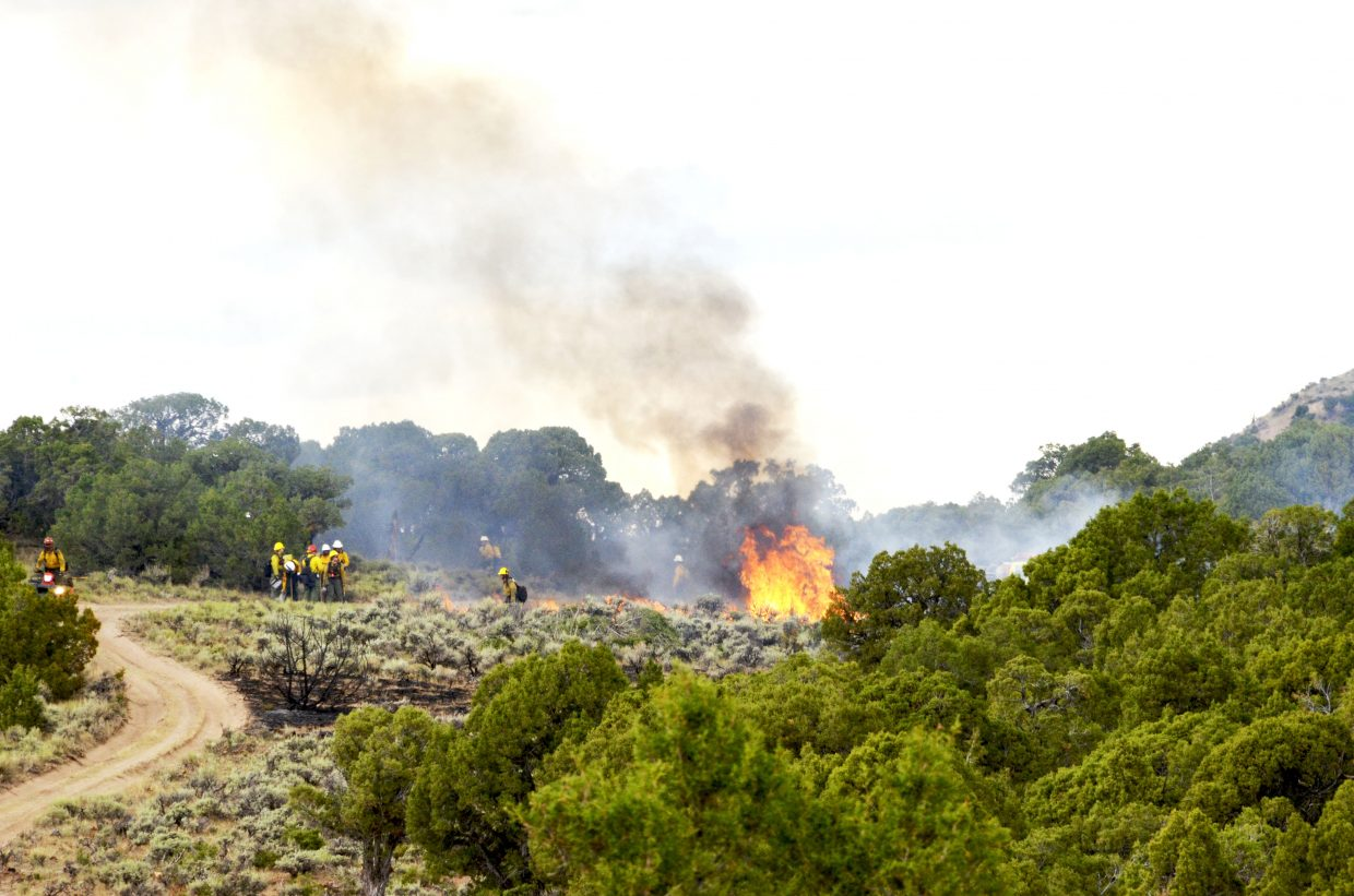 A fire crew manages the Kodiak Fire, burning approximately 25 miles northwest of Maybell