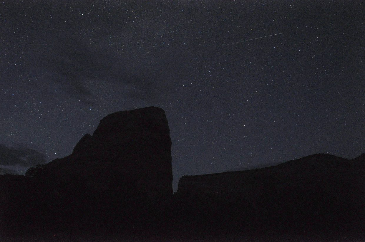 A meteor streaks across the sky above Steamboat Rock in Dinosaur National Monument.