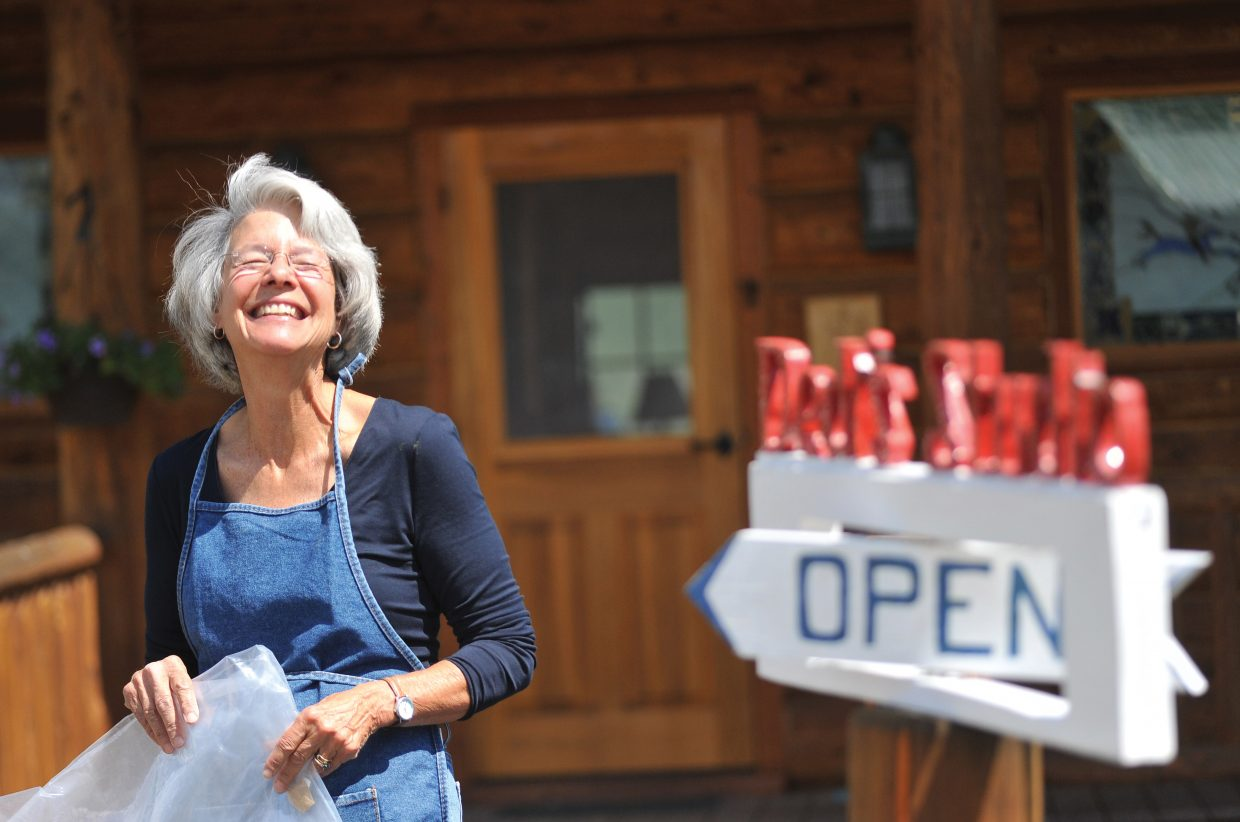 Artist Dedi Knox laughs near a sign welcoming visitors to her Hahn's Peak studio in North Routt County.