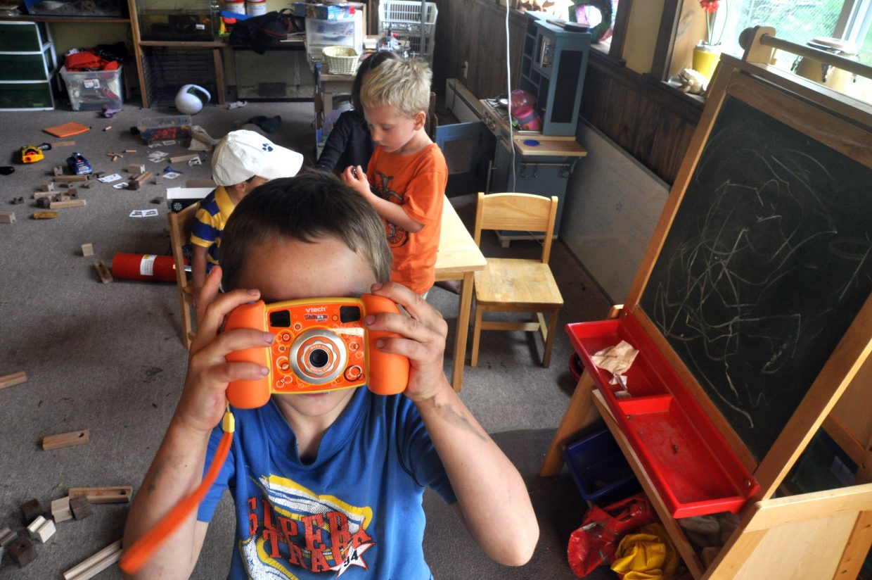 Gannon Skorkowsky snaps a few photos in the game room at his home in Oak Creek.