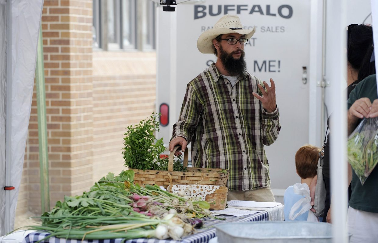 Jeremy Johnston talks with a customer at the Cacklin' Hen Farm booth Saturday at the Mainstreet Farmers Market in downtown Steamboat Springs. The Strawberry Park farm is a regular at the summertime market.