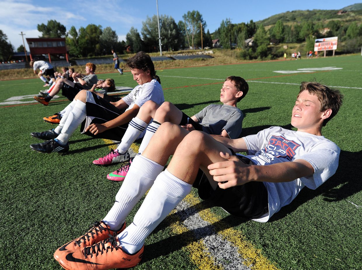 Steamboat Springs High School sophomore Jack Salyer grimaces through situps during the first day of practice Monday for the Sailors boys soccer team. Workouts began for most Routt County high school fall sports teams Monday, and competition for many of the teams will start at the end of the month.