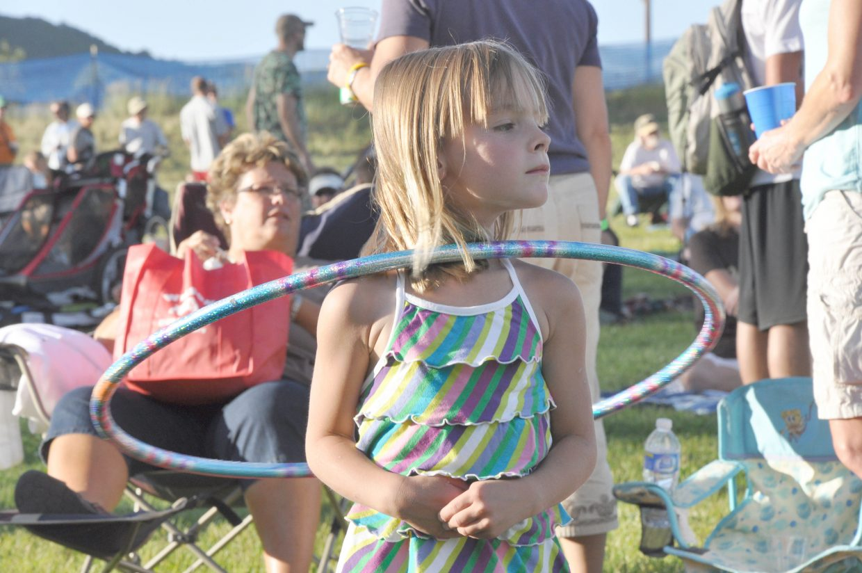 Catcher Weynand, 5, twirls a hula hoop as she watches the Free Summer Concert Series event on Friday at Howelsen Hill. JJ Grey performed with his blues band, Mofro.