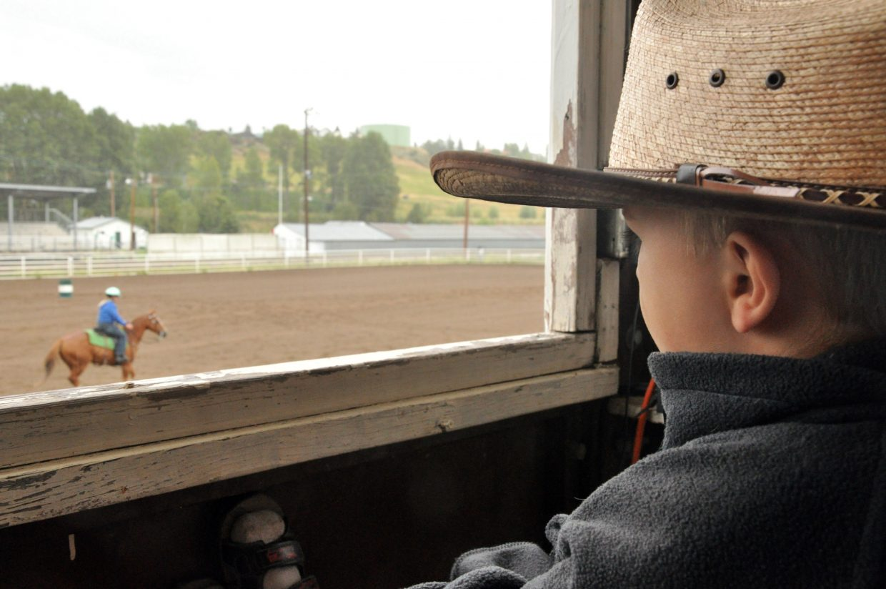 Eisten Gittleson watches a rider participate in an open horse show Sunday at the Routt County Fairgrounds.