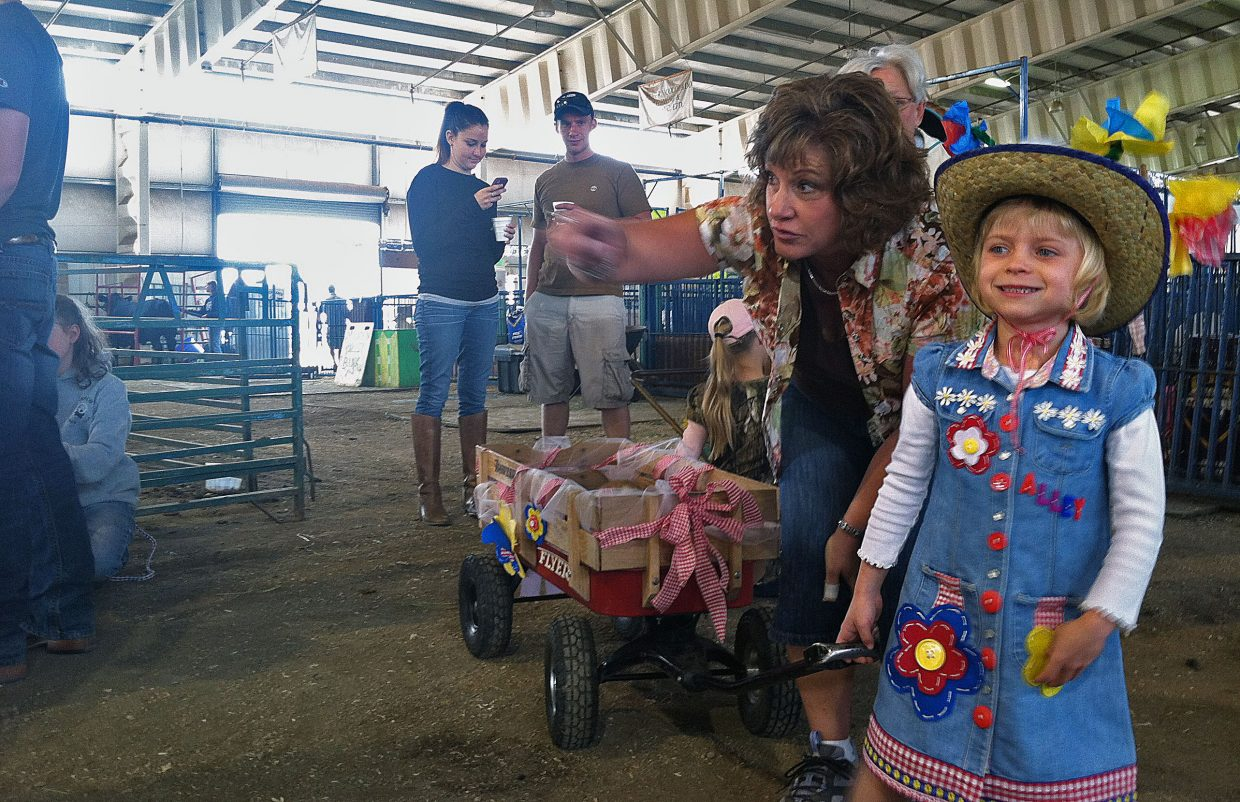 Ann Kvols points something out to Alley, 6, before the start of the Dress Your Animal Contest on Friday at the Routt County Fair in Hayden. Muffin, the rabbit, hides in Alley's wagon.