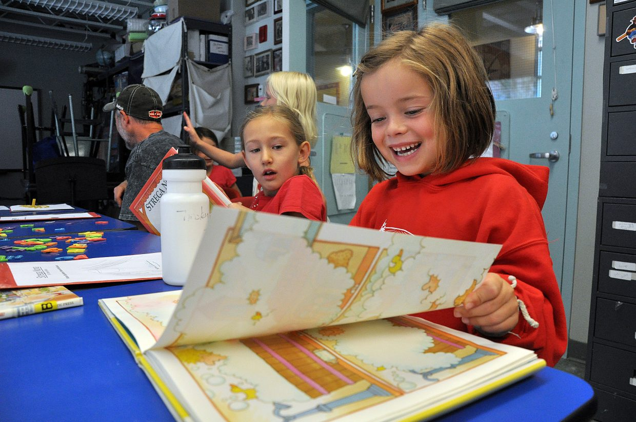 "Tinsley Moore laughs Thursday as she reads ""Strega Nona"" during the Emerald Mountain School's summer cooking camp. Enrollment at Emerald Mountain School currently is down five students, but Head of School Sharon Mensing said there's still plenty of time to fill the open spots before classes start at the end of this month."