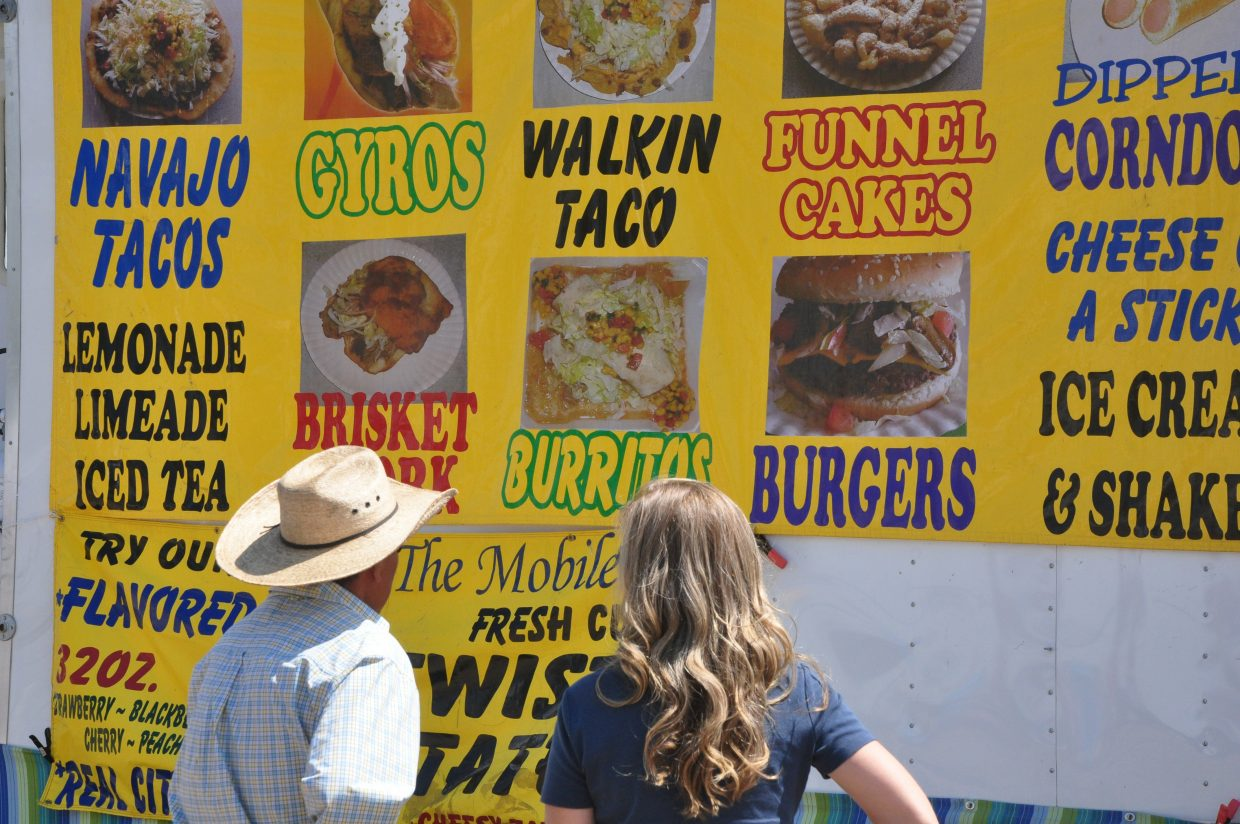 Fairgoers decide what to eat as they stare at a giant menu Friday at the Routt County Fair in Hayden