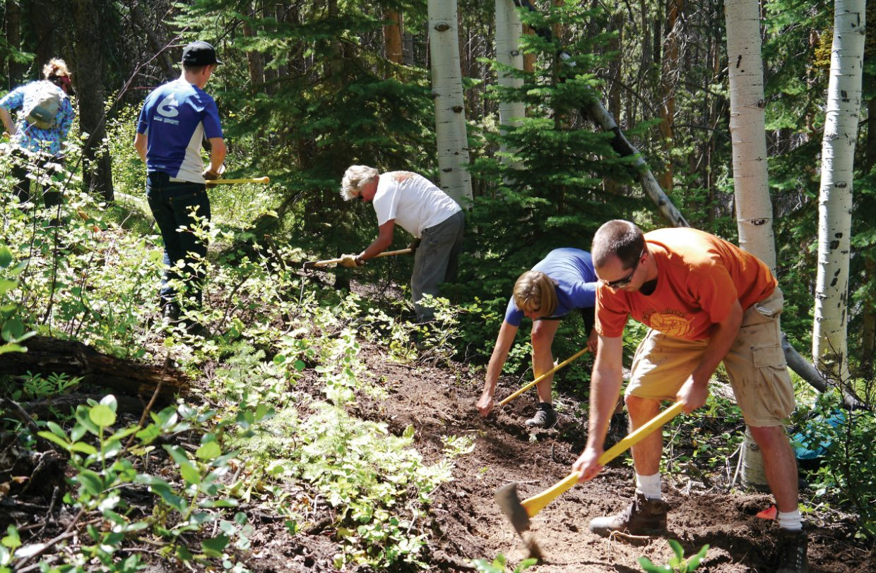 A group of volunteers builds a trail July 13 on Emerald Mountain as part of an International Mountain Bicycling Association sustainable trail building class.