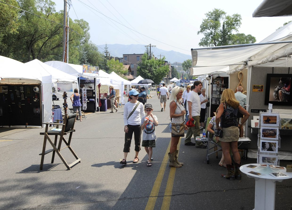 People visit artists during the Yampa River Art Stroll at the All Arts Festival on Friday on Yampa Street.