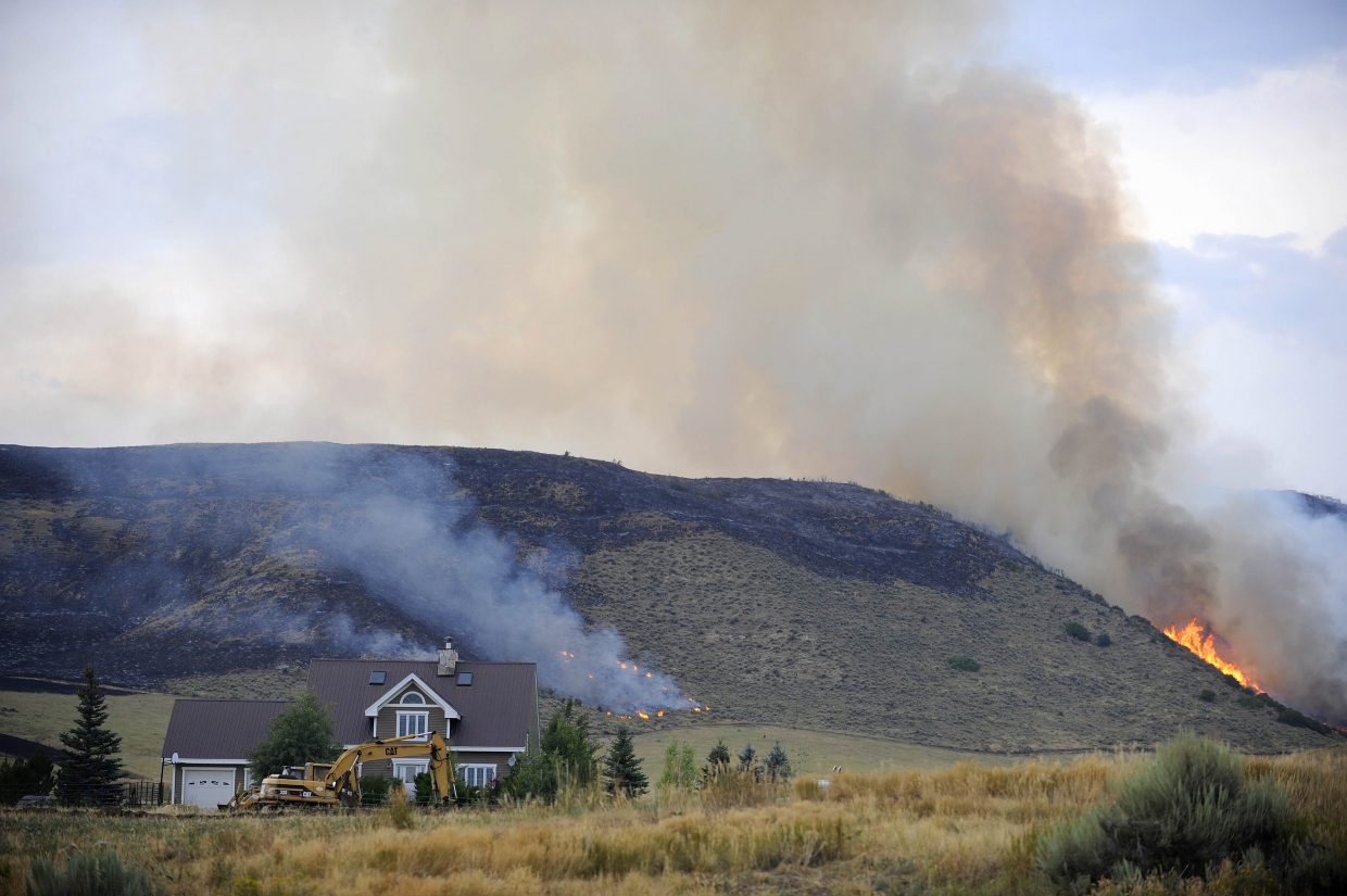 Fire burns on a hillside Saturday near the Zehner home off of C.R. 74.