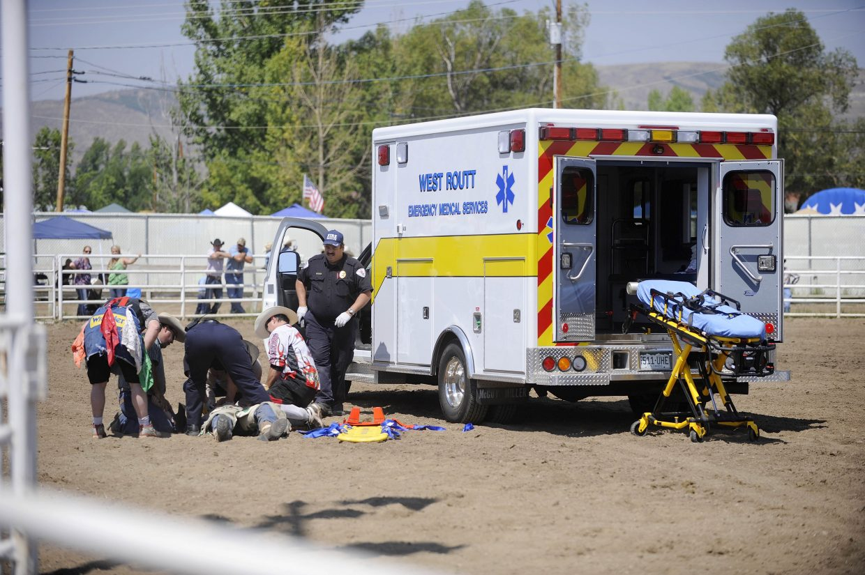 People attend to Craig bull rider Robert Baker after he was stomped on by a bull Saturday at the Routt County Fair.