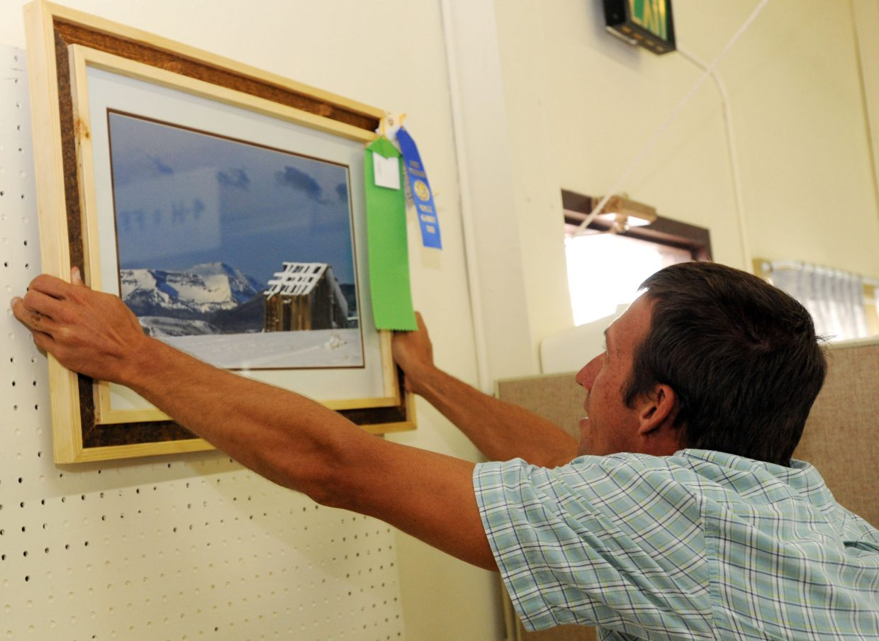 Greg Backes hangs an award-winning photo for the photography contest Thursday at the Routt County Fair in Hayden.