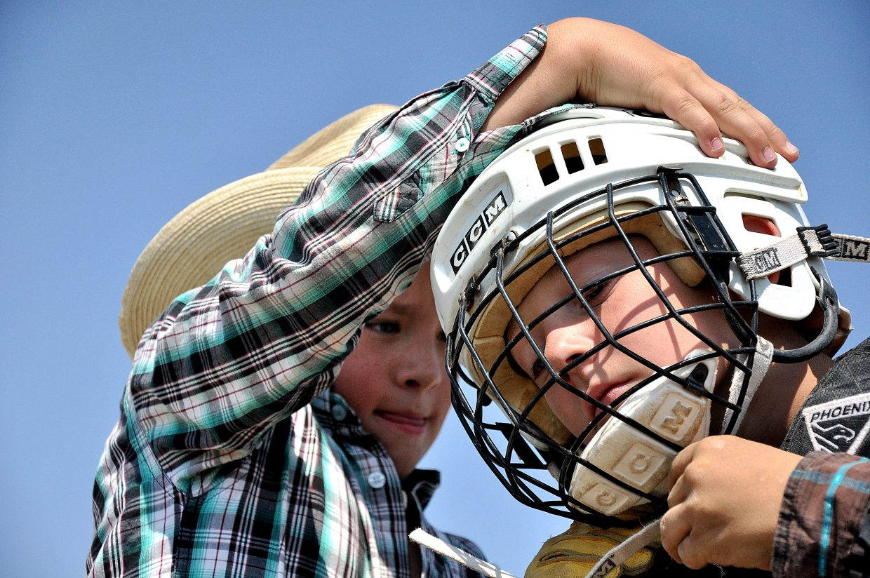 Jace Booco, left, helps his friend Keenan Hayes tighten his helmet Sunday before a ride on a steer at the Routt County Fair in Hayden.