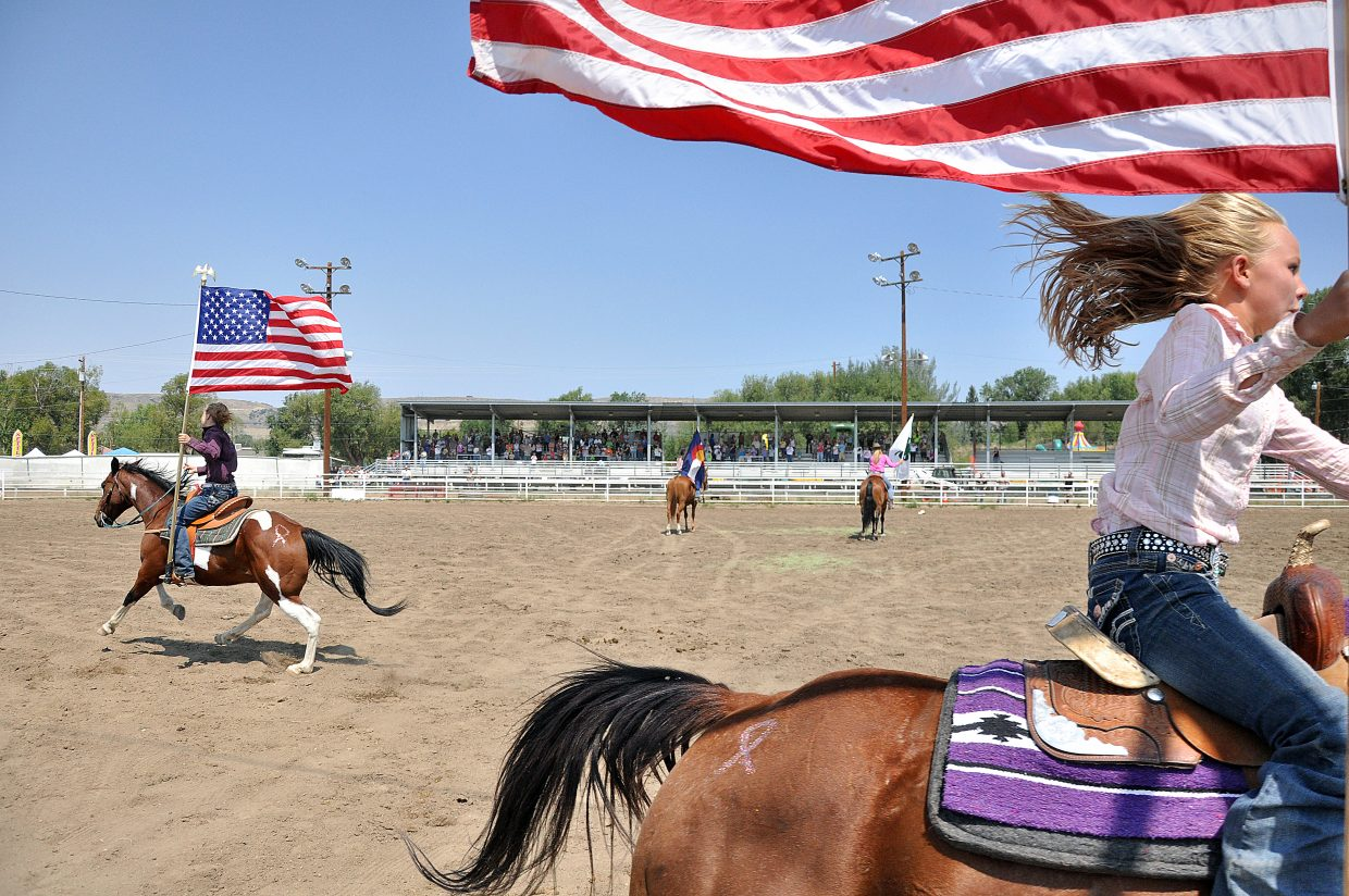 Karyn Forbes, right, and Kaitlynn Hayes ride with American flags Sunday during the singing of the national anthem at the Routt County Fairgrounds in Hayden.