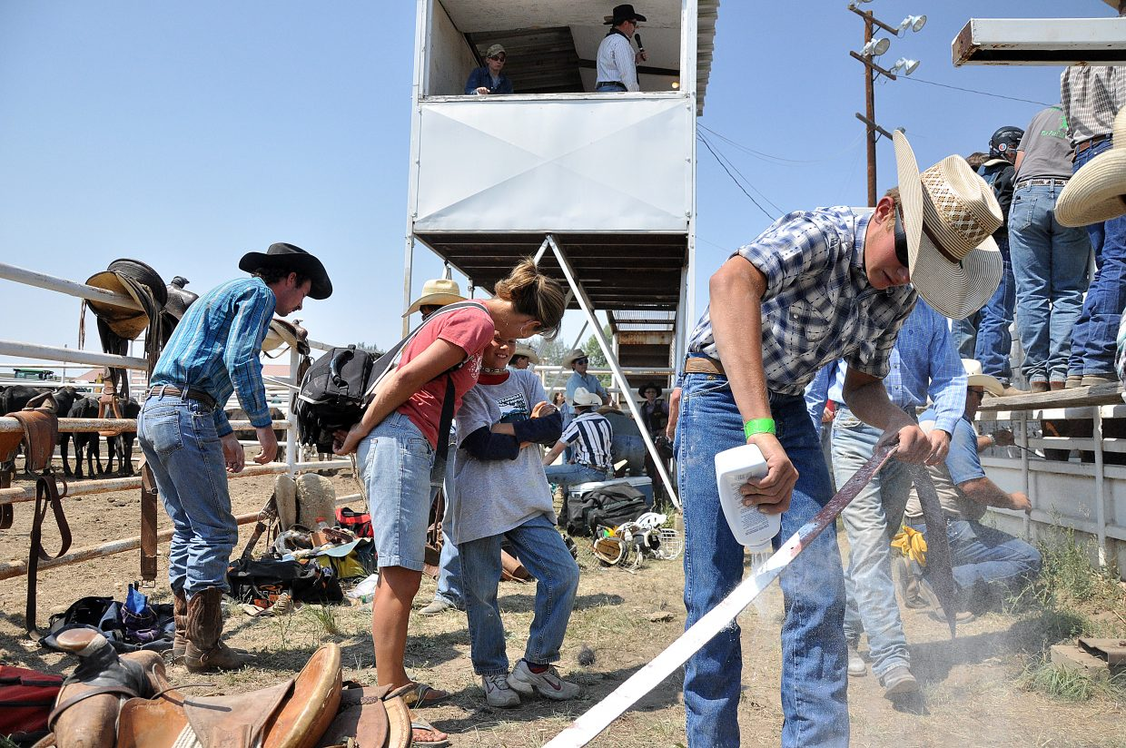 Jakob Sober pours baby powder on a latigo Sunday before the saddle bronc riding at the Routt County Fair in Hayden.
