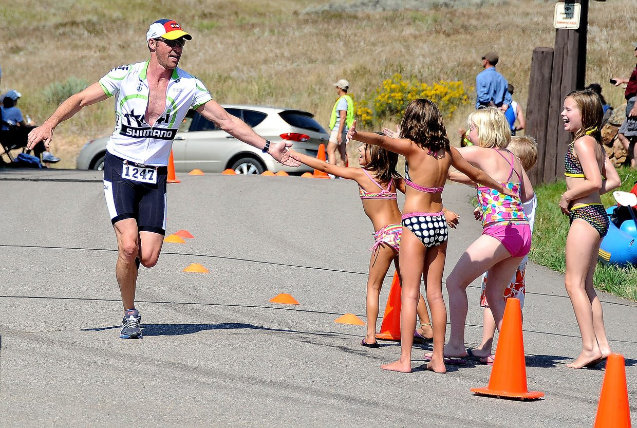 Denver athlete Ryan Pollock high-fives his fans near the finish line of Sunday's Steamboat Triathlon.
