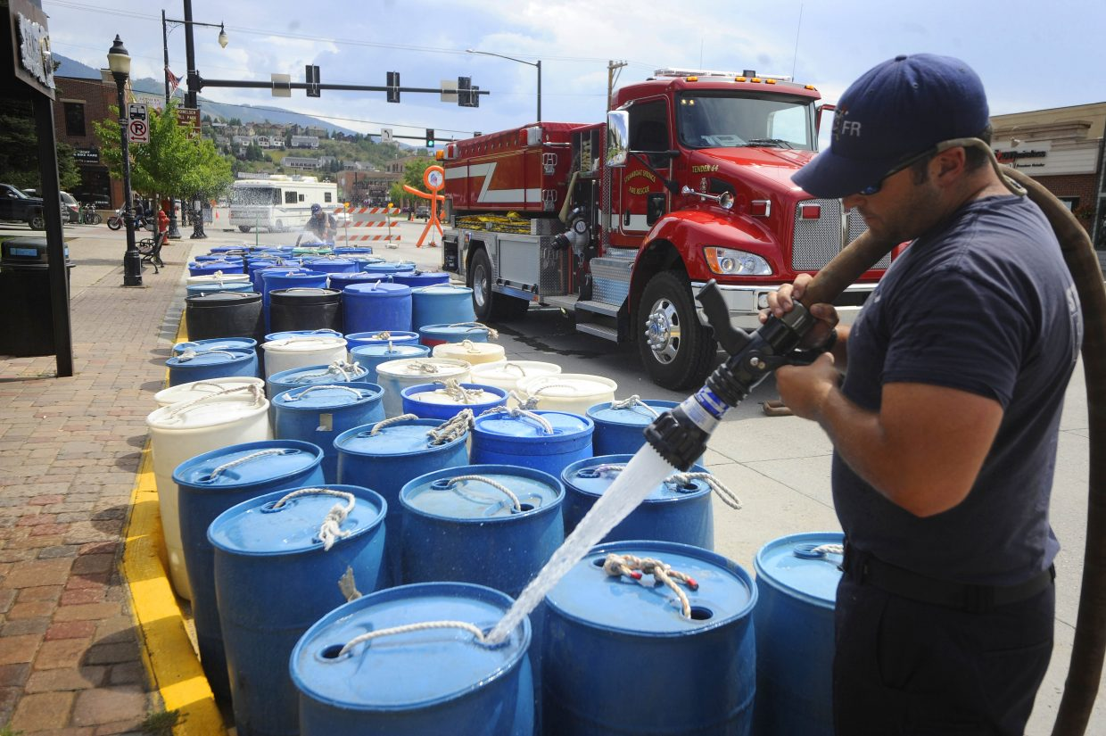 Steamboat Springs Fire Rescue firefighter Chris Welch fills barrels with water while helping set up for the USA Pro Challenge's arrival Wednesday in Steamboat.