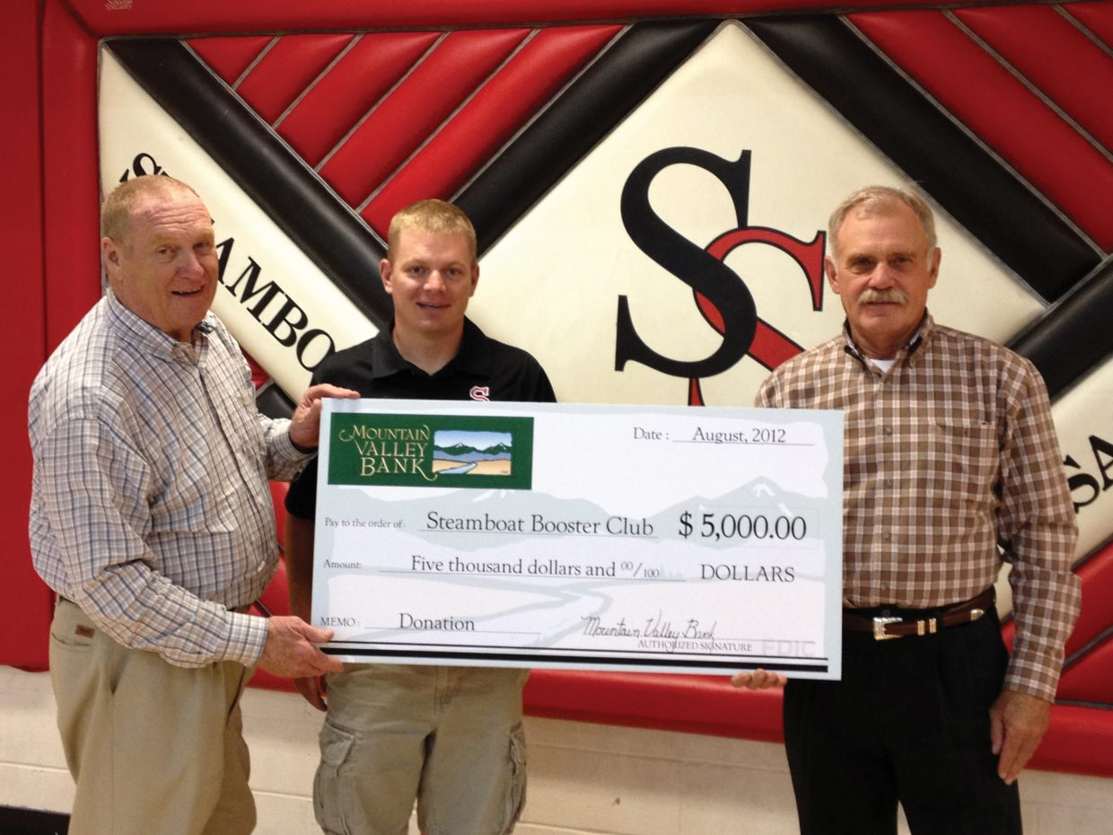 Dean Vogelaar, left, president of Mountain Valley Bank in Steamboat Springs, and Terry Jost, right, CEO and chairman of the board for Mountain Valley Bank, awarded Steamboat Springs High School Athletics Director Luke DeWolfe with a check for $5,000 this week. The money is for the high school's Booster Club and, specifically, to help cover the $30,000 needed to fully fund athletic team transportation costs during the upcoming school year. Vogelaar and Jost said they hope Mountain Valley Bank's donation will help kick-start other fundraising efforts by the Booster Club, including the discount card sales that just now are under way. For more information about the Booster Club or to donate, email Scott Glynn at steamboathockeyref@zirkel.us.