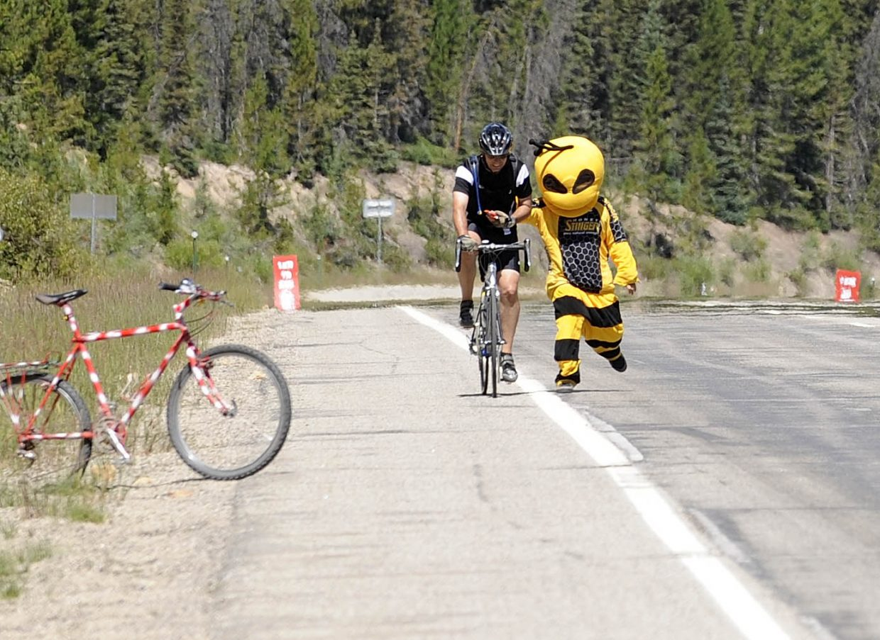 Honey Stinger's Buzz the Bee gives Niwot cyclist Bruce Wittich a hand near the east summit of Rabbit Ears Pass on Wednesday during the USA Pro Challenge.