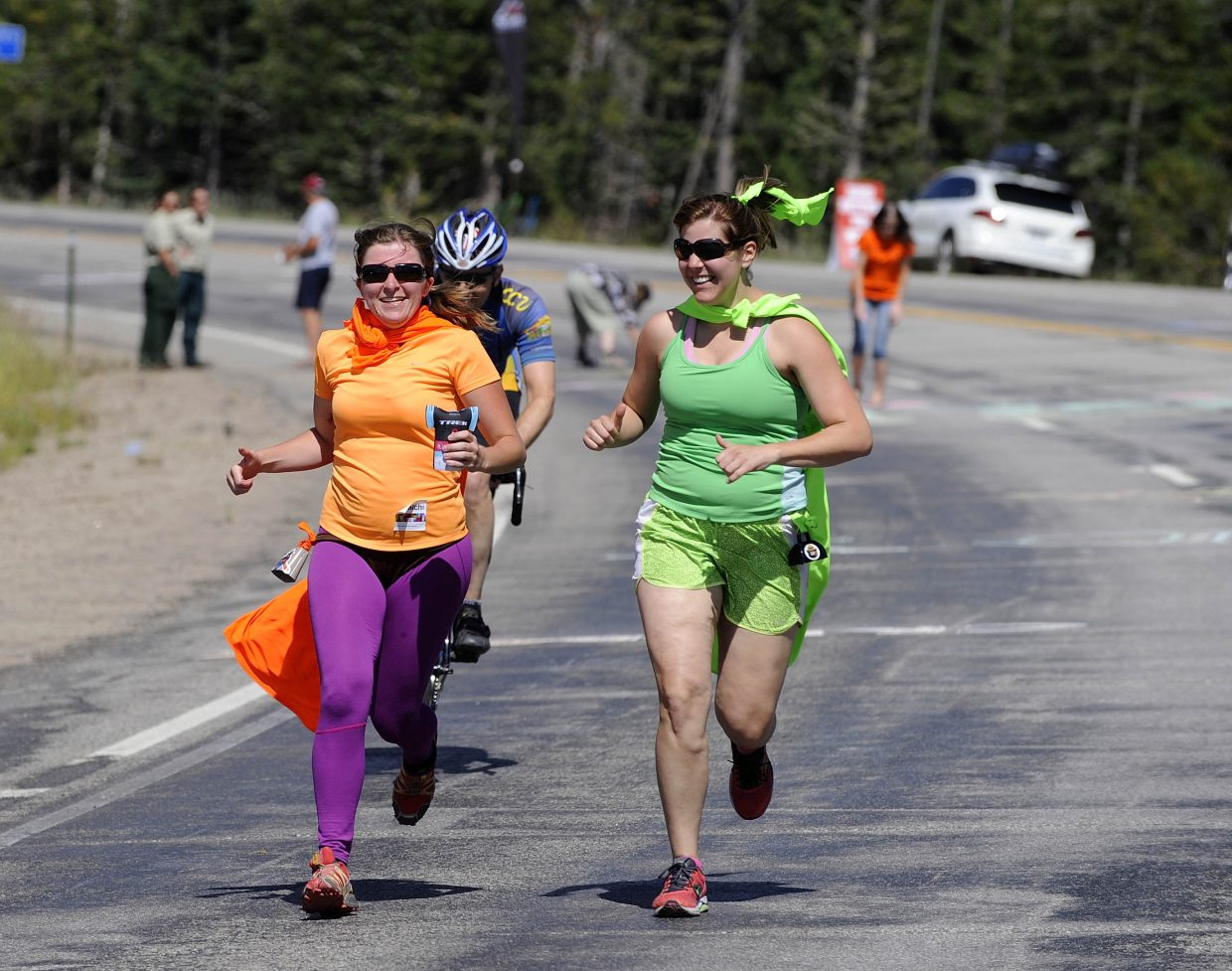 Maddy Marsh, left, of Vail, and Kara Shell, of Ohio, run with cyclists at the east summit of Rabbit Ears Pass on Wednesday during the USA Pro Challenge.