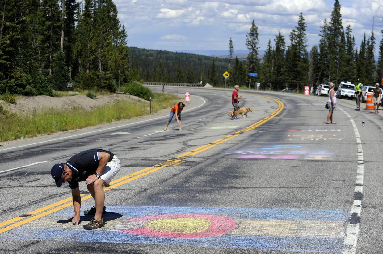 Peter Spurlin, of Fort Collins, uses chalk to draw the Colorado flag at the east summit of Rabbit Ears Pass on Wednesday during the USA Pro Challenge.