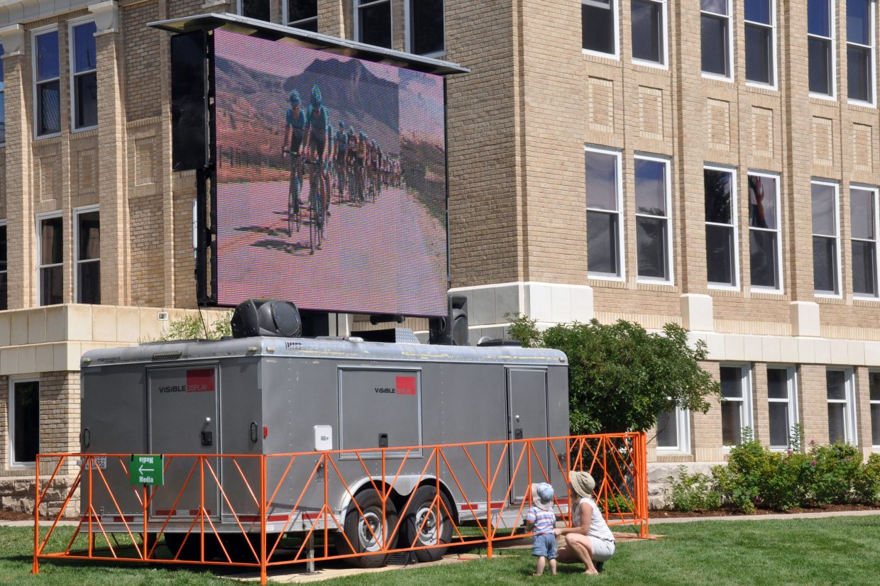Cortni O'Brien and her son, Evan, watch the USA Pro Challenge on a large screen in downtown Steamboat Springs.