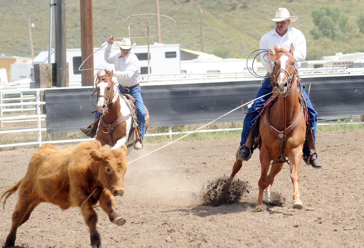 Cowboys from the White River Ropers try to wrap up a calf Sunday during the ranch rodeo at the Routt County Fair in Hayden.