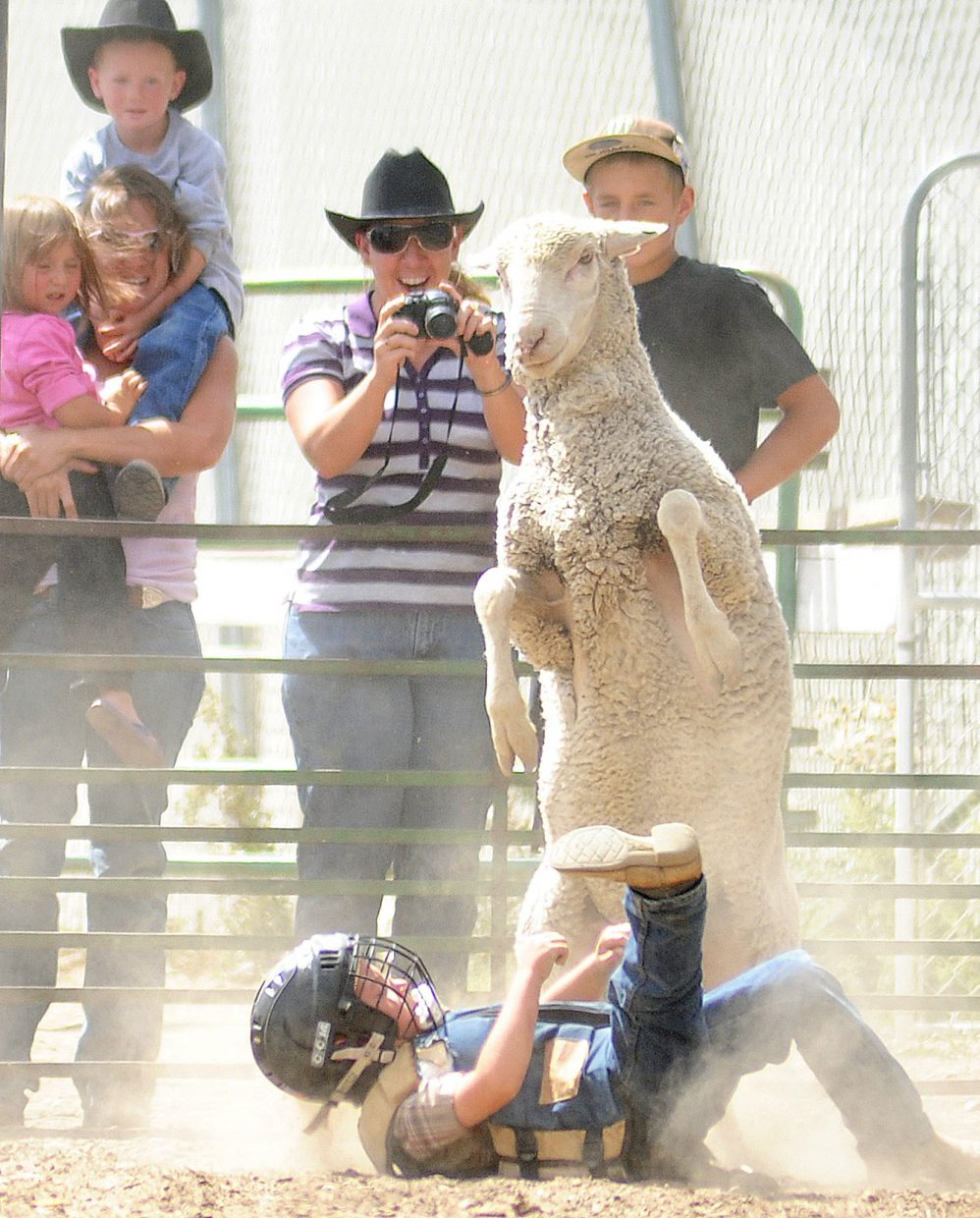 Dylan Brady lands hard after his ride in the mutton bustin' competition at the Routt County Fair in Hayden on Sunday.