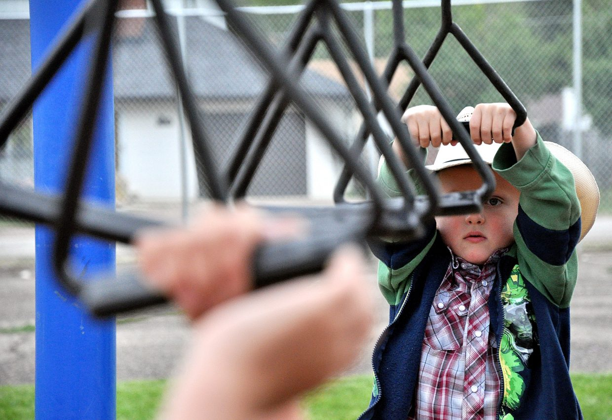 Camron Wisecup goes for a swing on the monkey rings Wednesday during the first day of classes at South Routt Elementary School in Yampa.
