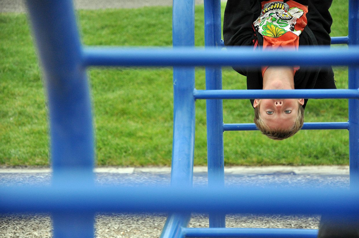 Alan Mayer hangs from the monkey bars Wednesday during the first day of school at South Routt Elementary School in Yampa.