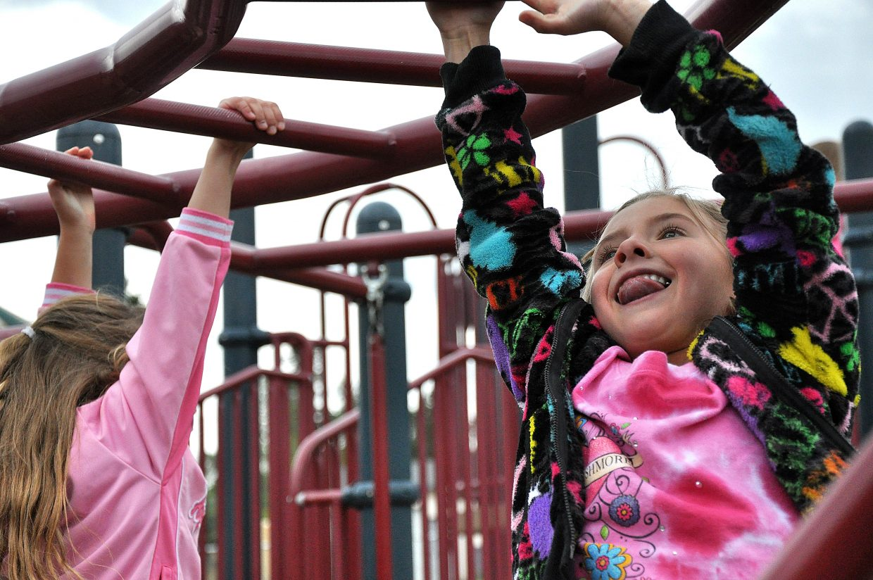 Joanna Almeida hangs from the monkey bars Wednesday during the first day of school at South Routt Elementary School in Yampa.