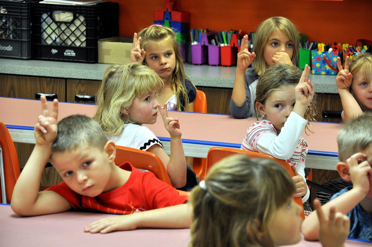First-grade students at South Routt Elementary School put up peace signs Wednesday during art class.