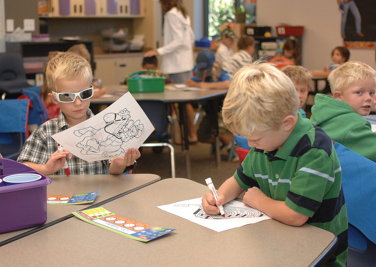 First grader Olin Webster colors pictures along with fellow student James Appel on the first day of class Wednesday at Soda Creek Elementary School.