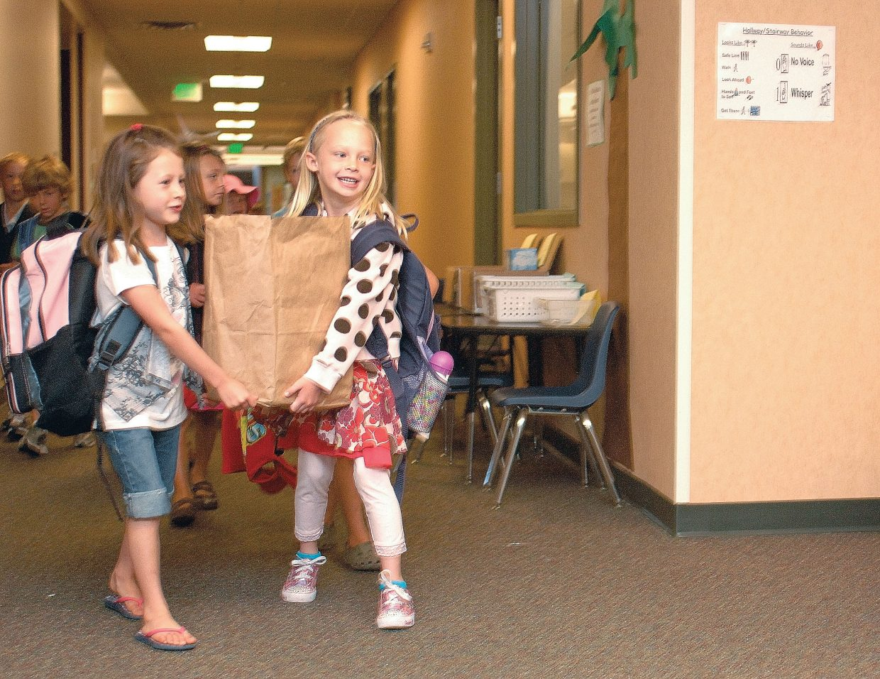 First grader Allie Van Ness, right, gets a helping hand from classmate Norah Pietras while carrying supplies to class on the first day of school Wednesday at Soda Creek Elementary.