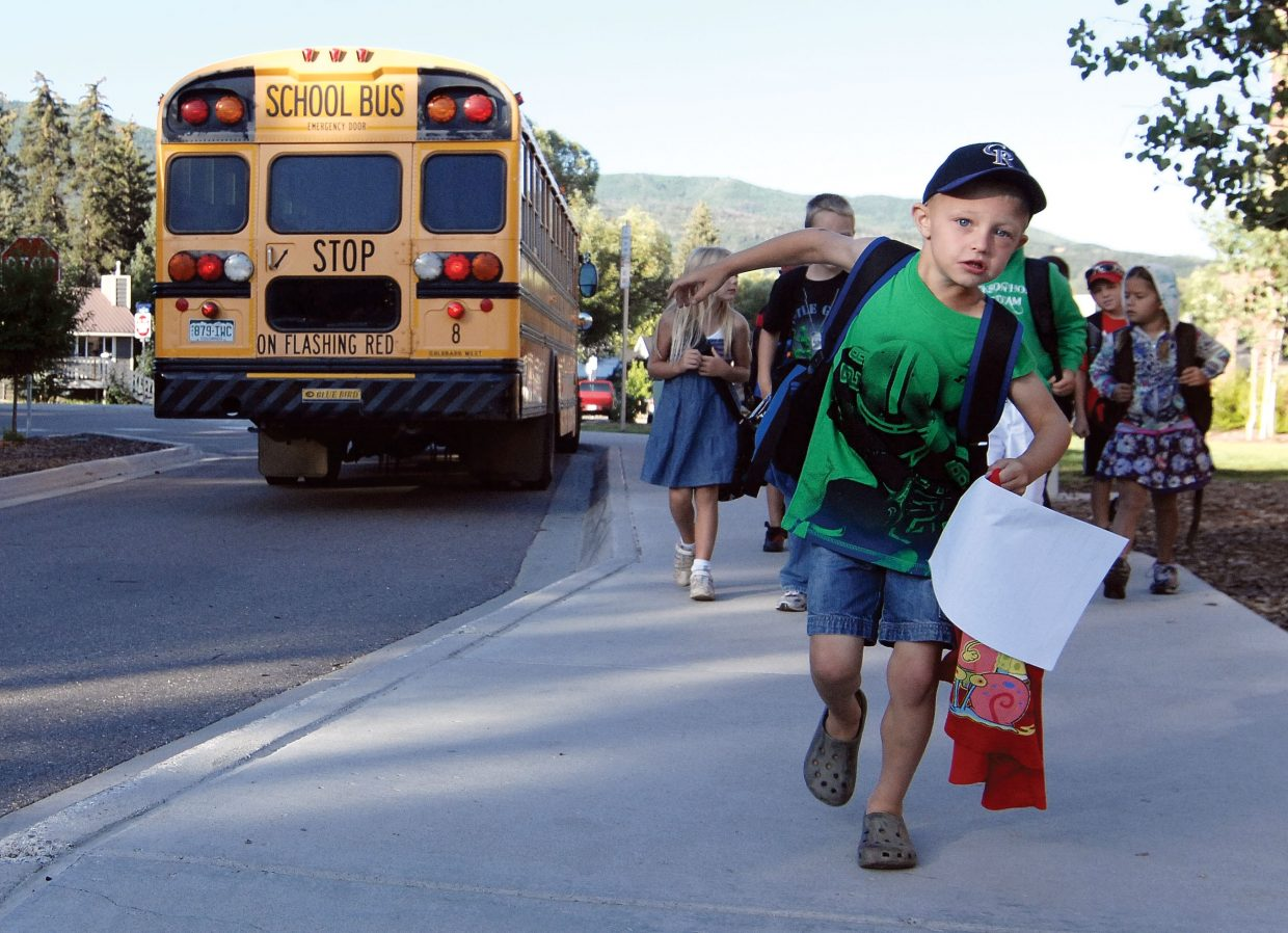 First grader Cole Muhme runs from the school bus to the playground Wednesday on the first day of classes at Soda Creek Elementary School in Steamboat Springs. Students across the city headed back to school for the first day of the 2011-12 school year.