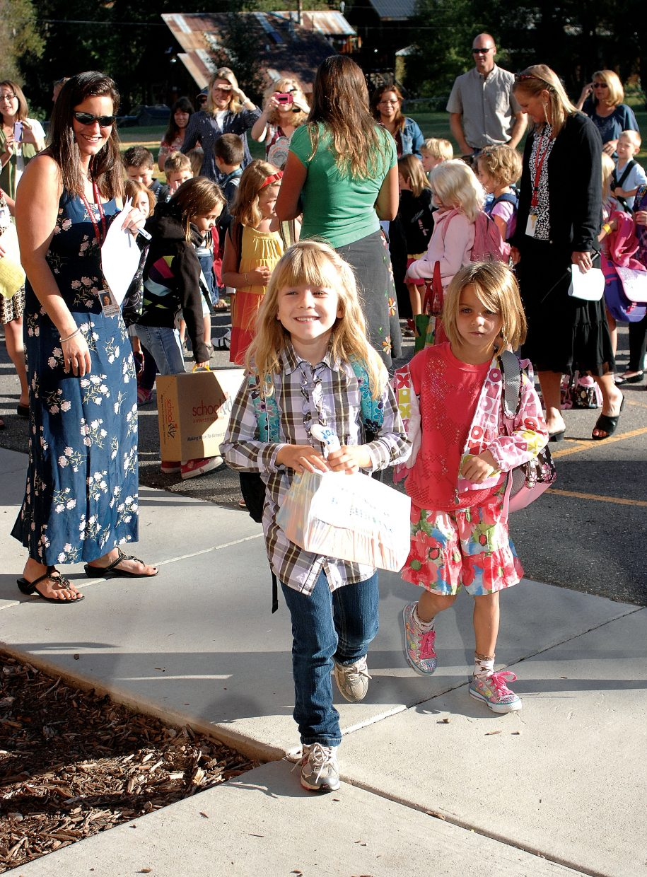 Kaelley Freideman and Avery Duty make their way into Soda Creek Elementary School on Wednesday on the first day of classes. Students across the city headed back to school for the first day of the 2011-12 school year.