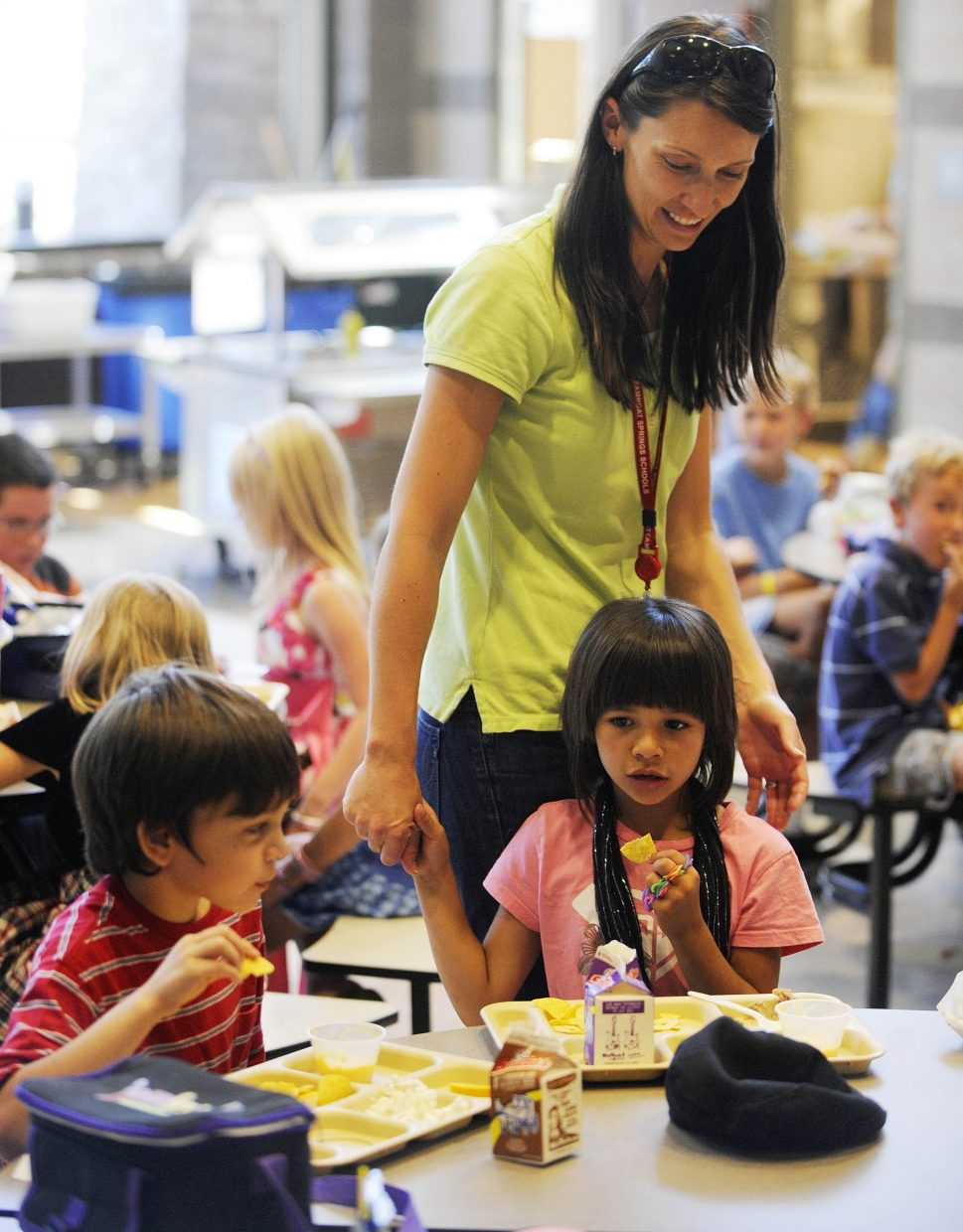 Soda Creek Elementary School second-grader Kaedynce Kaleikini reaches her hand out to new second-grade teacher Aurora King during lunch on the first day of school Wednesday.